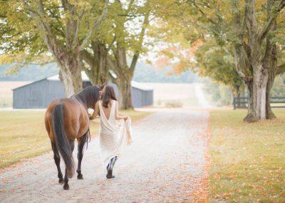 Bride leading horse down driveway